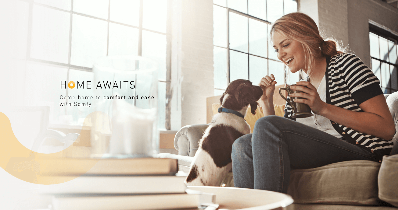 Campaign visual of a girl holding a coffee and bending down to interact with her dog whilst in her home with the campaign tagline home awaits